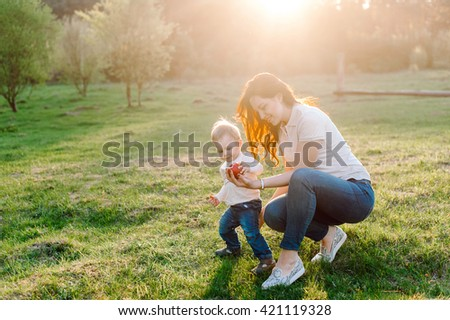 Happy family walking outdoor. Young mother gives her son an apple in hand. The setting sun. Warm summer evening - stock photo
