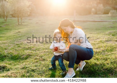 Happy family walking outdoor. Young mother gives her son an apple in hand. Warm summer evening - stock photo