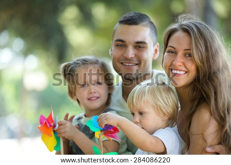 Happy family walking through park on vacation day - stock photo