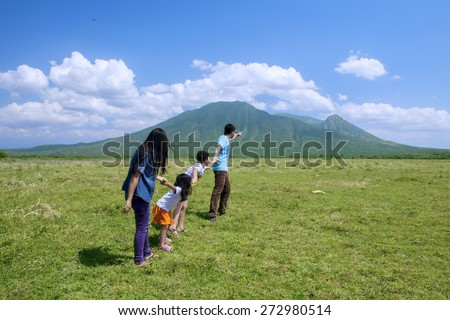 Happy family walking to the mountain while holding hands - stock photo