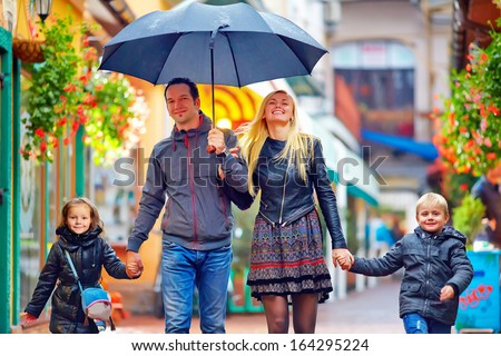 happy family walking under the rain on colorful street - stock photo