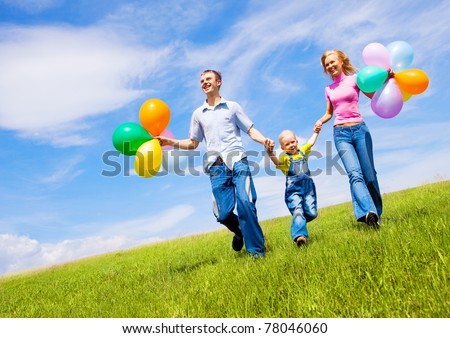 happy family walking with balloons outdoor on a warm summer day