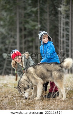Happy family walking with dog in late autumn nature. focus on boy - stock photo