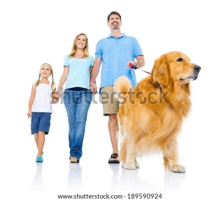 Happy Family Walking With Golden Retriever Dog - stock photo