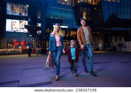 happy family walking with paper bag in front of  shopping mall