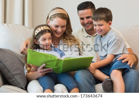 Happy family watching photo album together while sitting on sofa at home