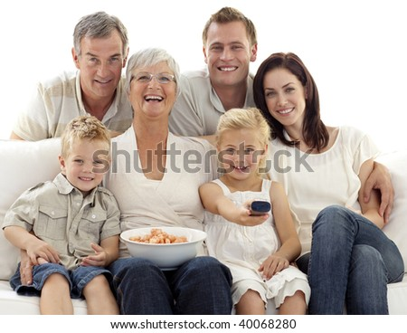 Happy family watching television and eating chips at home - stock photo