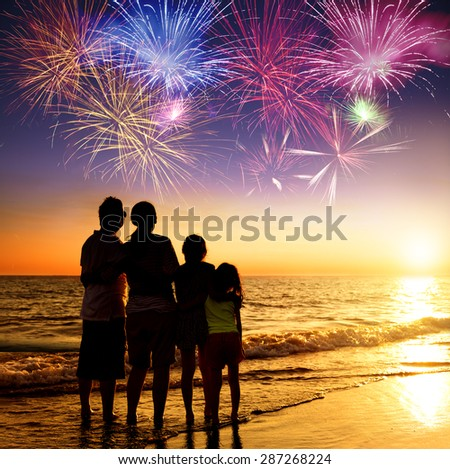 happy family watching the sunset and firework on the beach - stock photo