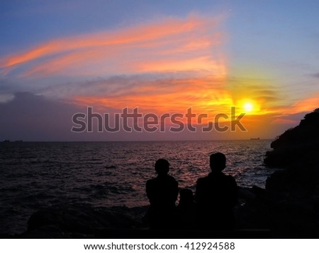 Happy family watching the sunset over the sea. Happy family concept.