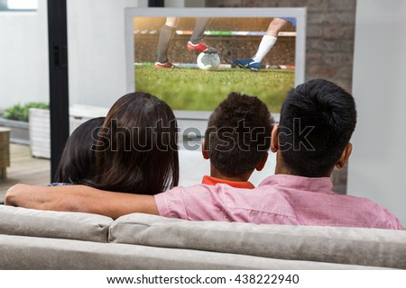 Happy family watching tv on the sofa against football players tacakling for the ball on pitch - stock photo