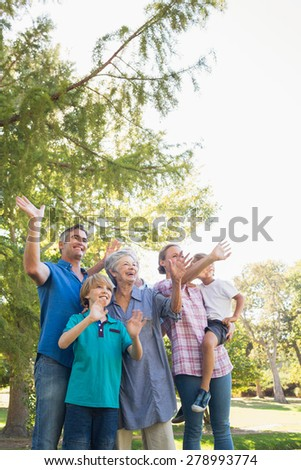 Happy family waving hands in the park on a sunny day