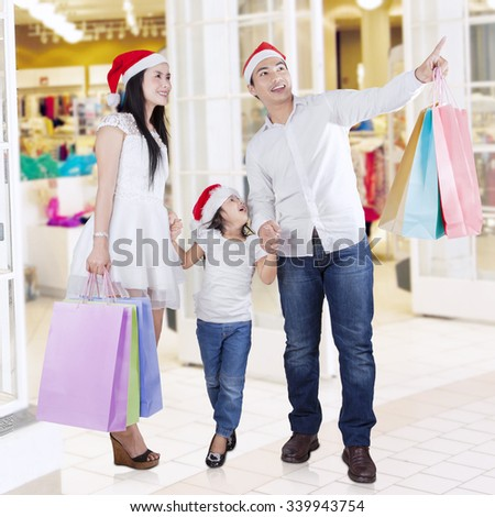 Happy family wearing santa hat and carrying shopping bags while looking something at mall - stock photo