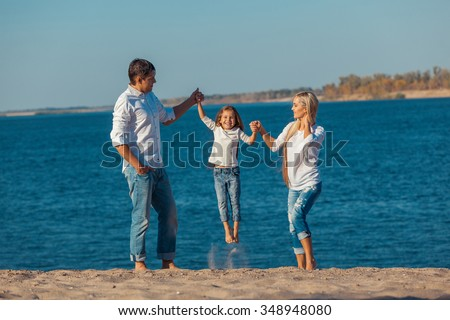 Happy family who playing on the beach. Concept of friendly family. - stock photo