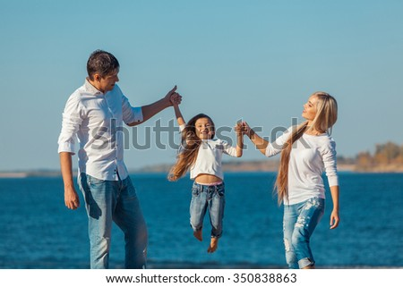 Happy family who playing on the beach. Concept of friendly family.