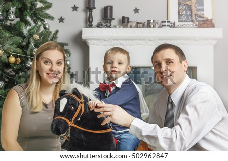 Happy family with a child in the New Year's interior in a Christmas tree with decorations