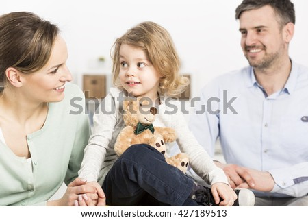 Happy family with a mother and her little daughter holding a teddy bear in the foredground