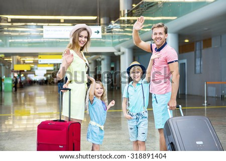 Happy family with a suitcase at the airport - stock photo