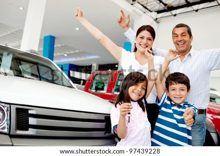 Happy family with arms up celebrating having a new car - stock photo