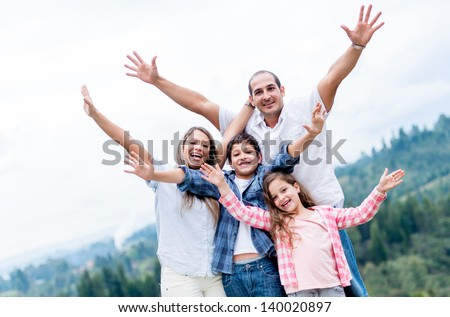 Happy family with arms up outdoors celebrating