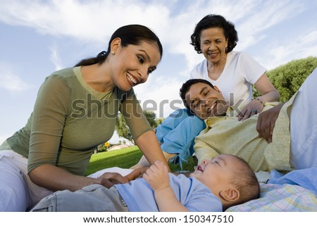 Happy family with baby boy relaxing in park - stock photo
