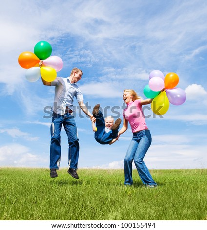 happy family with balloons  jumping outdoor on a warm summer day - stock photo