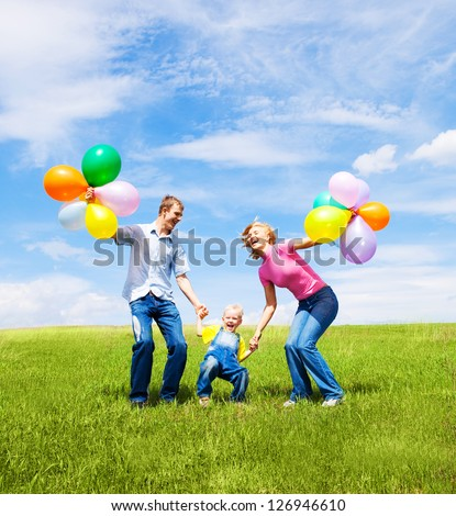 happy family with balloons  jumping outdoor on a warm summer day