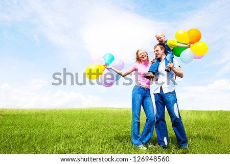 happy family with balloons outdoor on a warm summer day