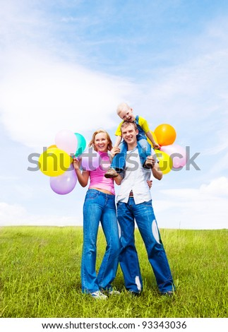 happy family with balloons  outdoor on a warm summer day - stock photo