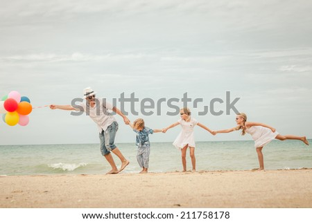 Happy family with balloons playing on the beach at the day time. Concept of friendly family. - stock photo