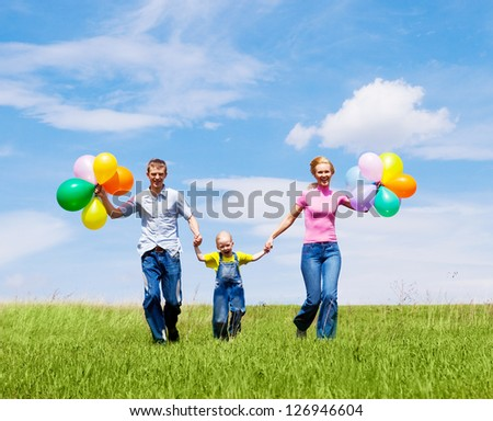 happy family with balloons running outdoor on a warm summer day - stock photo