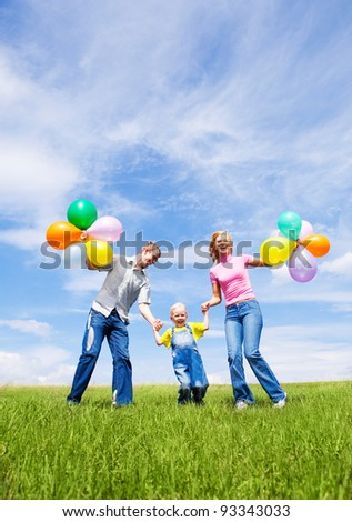 happy family with balloons running outdoor on a warm summer day