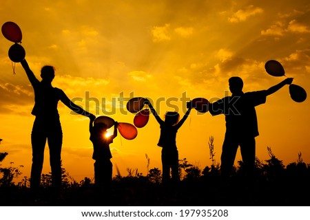 Happy  family  with balloons  standing on the road at the  sunset time. Evening party on the nature - stock photo