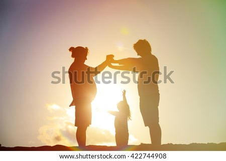 Happy family with child and pregnant mother together at sunset - stock photo