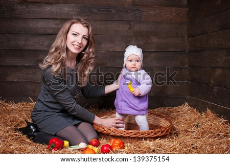 Happy family with  child - beautiful mother  hug with her daughter , posing on hay in studio closeup - stock photo