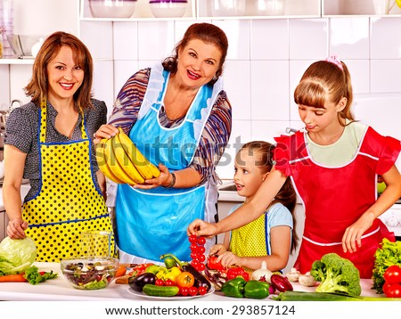Happy family with child cooking at kitchen. Grandfather and grandmother. Four people. - stock photo