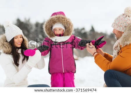 happy family with child in winter clothes outdoors - stock photo