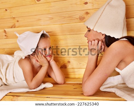 Happy family with child relaxing at sauna. - stock photo