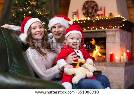 Happy family with child sitting on sofa a fun near Christmas tree and fireplace  in living room
