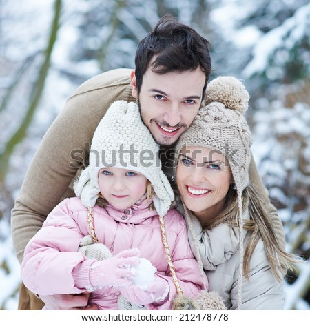 Happy family with child smiling outdoors in winter snow - stock photo