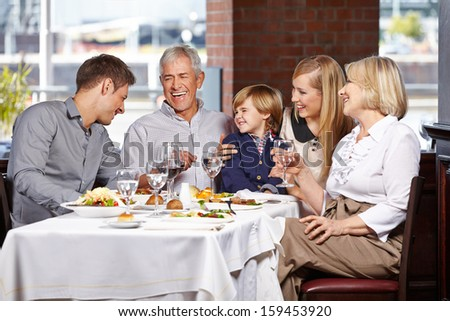 Happy family with child smiling together in a restaurant - stock photo