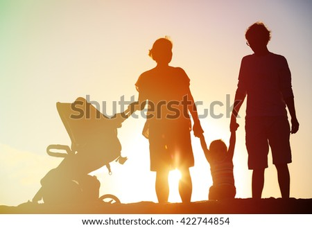 Happy family with child together at sunset