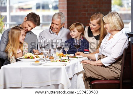 Happy family with children and seniors eating out in a restaurant - stock photo