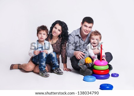 Happy family with children  - beautiful mother and father hug their sons, posing on white background  in studio closeup - stock photo