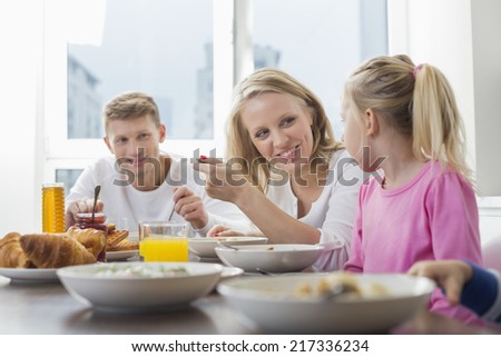Happy family with children having breakfast at table - stock photo