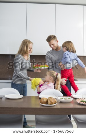 Happy family with children having meal in domestic kitchen - stock photo