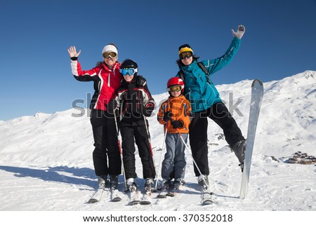 Happy family with children in a ski resort on sunny day - stock photo