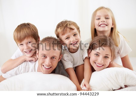 Happy family with children in bed - stock photo