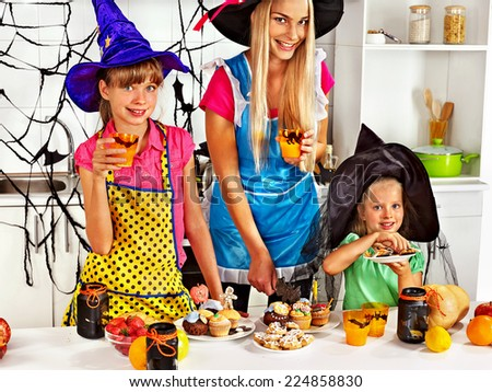 Happy family with children preparing halloween food. - stock photo