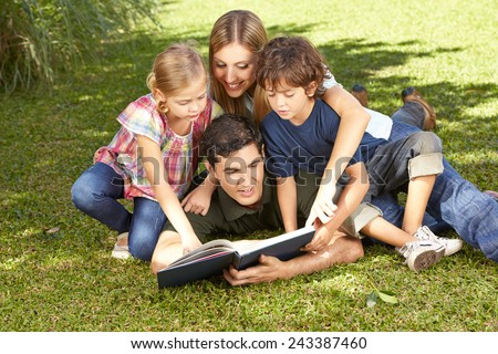 Happy family with children reading a book together in a garden - stock photo