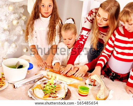 Happy family with children rolling dough in Christmas kitchen.